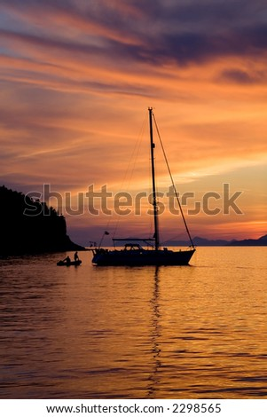 Two people climbing on a sailboat during a gorgeous sunset.