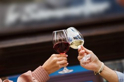 Two people clinking glasses with red and white wine