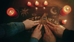 Two people conducting a seance using a Ouija Board, or Talking Spirit Board, with red candles. Shot from overhead.