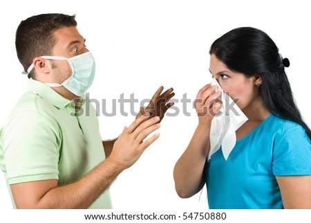 Two people couple in a situation :woman sneeze in a white napkin while the man wearing a protective mask and it is very scared trying to stop her sneezing with his hands
