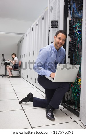 Two people doing data storage with laptops