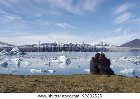 Two people enjoying the view of icebergs in Jokulsarlon, Iceland