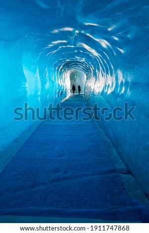 Two people exiting a blue ice tunnel in the Mer de Glace glacier remade every season in Chamonix France Photo stock ©