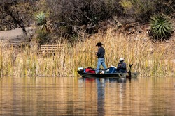 Two people fish from a small boat at Patagonia Lake State Park, Arizona. Both men are wearing face coverings. Their boat is overfilled with gear. Concepts of outdoor recreation, fishing, state parks