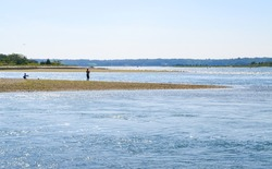 Two people fish on a spit of land jutting across the image. In the distance lies the mouth of Stony Brook Harbor with its water sparkling from the summer sun. Copy space. Stony Brook, New York.