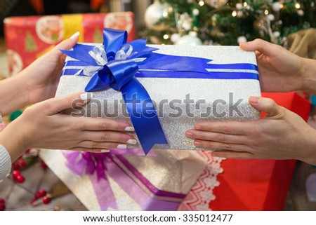 Two people giving gift box on Christmas during winter holiday.