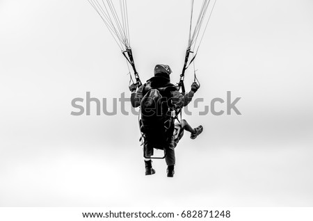 Two people hang gliding together; teamwork concept, trust concept, black and white image  #682871248