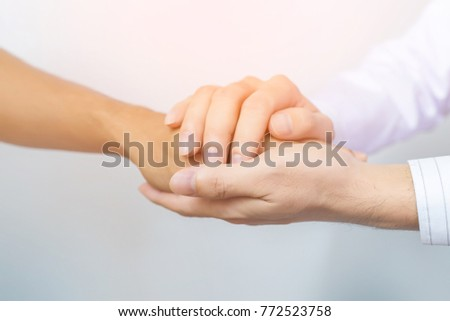 Two people holding hands for comfort. Doctor consoling relatives of patients in hospital concept