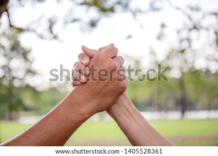 Two People Holding Hands in the Air to Greeting Power of Tag-Team. Close friend Joy Working Togetherness. Volunteer Collaboration in Project Team success.Teamwork Together Concept.
