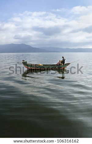 Two people in a fishing boat in the early morning in Dali, Yunnan Province, China