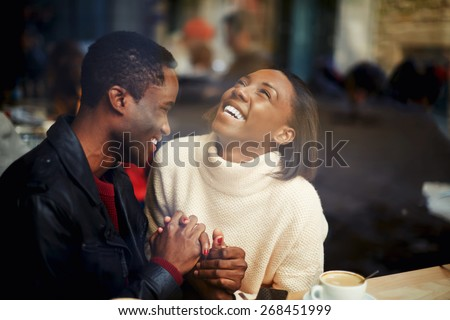 Two people in cafe enjoying the time spending with each other, happy stylish friends having coffee together, laughing young couple in cafe, having a great time together, view through cafe window