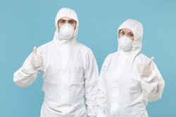 Two people in protective suits respirator masks isolated on blue background studio. Epidemic pandemic new rapidly spreading coronavirus 2019-ncov originating in Wuhan China medicine flu virus concept
