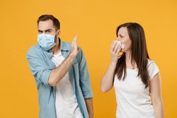 Two people in sterile face masks white t-shirts isolated on yellow background studio. Epidemic pandemic rapidly spreading coronavirus 2019-ncov medicine flu virus ill sick disease treatment concept