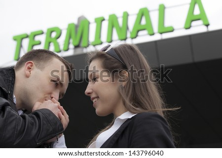 Two people in the airport. Man kissing woman's hand - stock photo