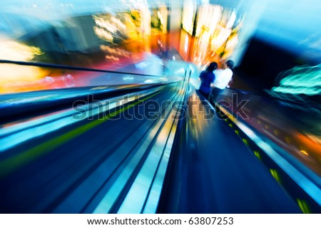 two people in two ways escalator,  because of photo shot by motion blur, the people can't be identify.