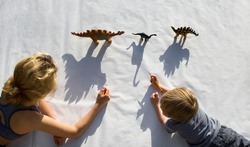 Two people lie side by side - a girl and a little boy - draw with a pencil around the contrasting shadows from the figures of toy dinosaurs. ideas for the development of creative thinking