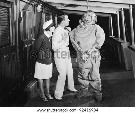 Two people looking in shock at a diver in a diver's suit