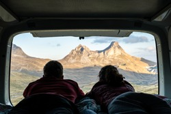 Two people lying in a camper van looking out towards the mountains during sunset Durmitor National Park