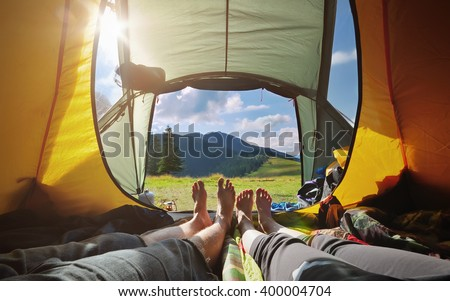Two people lying in  tent with a view of mountains. Carpathians, Ukraine