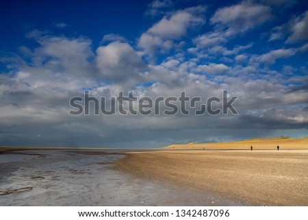 Two people making a beachwalk on the Maasvlaktestrand. This beach is a result of the creation of Maasvlakte 2. Maasvlakte 2 is the latest expansion of the Rotterdam harbour. #1342487096