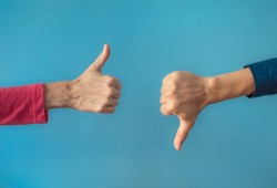 Two people making hand sign thumbs up and thumbs down, yes or no, like or dislike concept.