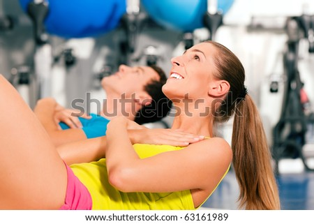two people, man and woman, exercising doing sit-ups in the gym for better fitness