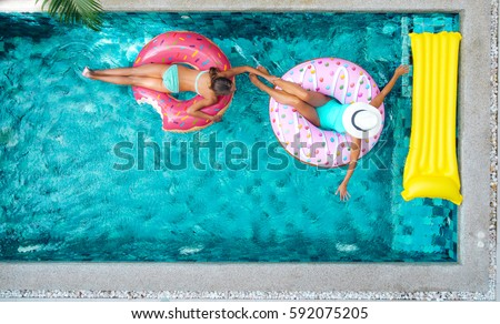 Two people (mom and child) relaxing on donut lilo in the pool at private villa. Inflatable ring and mattress. Summer holiday idyllic. High view from above. #592075205