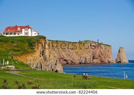 Two people on a bench observing the Red House on the cliff, and part of the  Percé Rock(Percé (city) Quebec, Canada