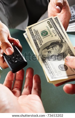 Two people on car transaction, one holding US dollar bills and another holding car alarm device