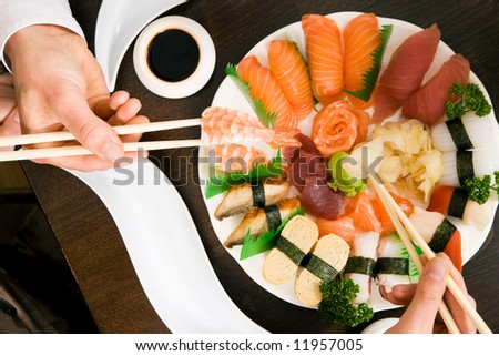 Two people (only hands to be seen) eating sushi; focus on the food