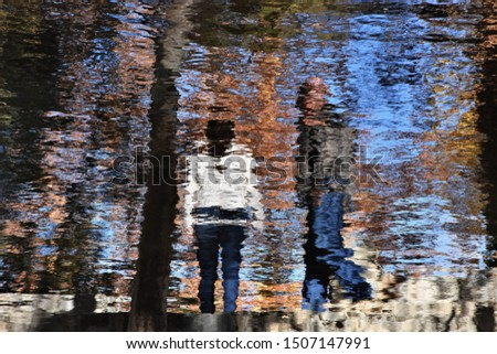 Two people reflected in a pond look like an impressionistic painting. #1507147991