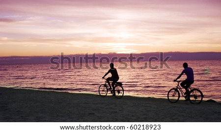 Two people rides by bicycles on the Baltic sea beach