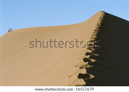 Two people riding a camel across desert, hoofprints in foreground