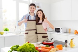 Two people romantic couple lovers chef gourmet man woman enjoy hobby weekend preparation tasty meal dinner approve show thumb-up sign in kitchen house indoors