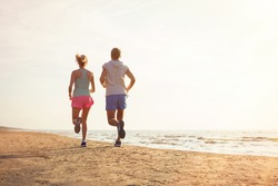 Two people running on the beach