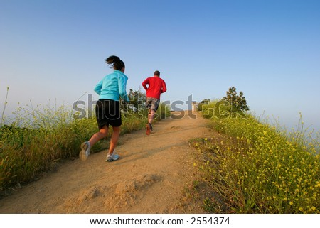 Two people running on the top of a hill