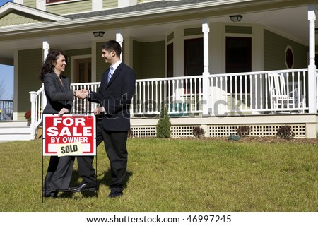 "Two people shake hands as they place a ""for sale"" sign in front of a house. This could be two realtors who have sold the house or a realtor and buyers."
