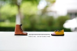 Two  people shoes keep distance with the word social distancing in between, Social distancing new normal concept, People keeping distance for infection risk and disease Coronavirus.