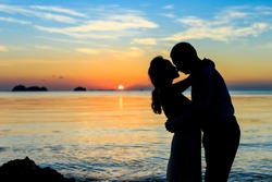 Two people silhouettes on beach  sunset