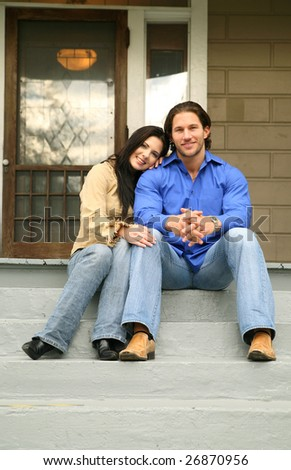 two people sit in front of their new house with happy expression