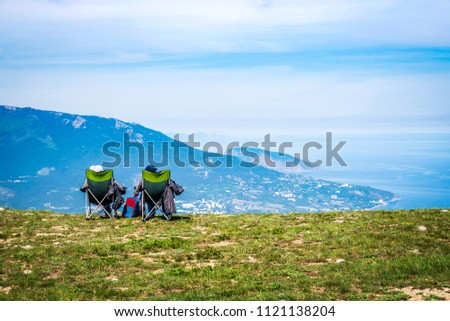 Two people sit on tourist chairs on the mountain and look at the sea. Aerial panoramic view of the city of Yalta in Crimea, Russia. Ayu-Dag or Bear Mountain in the background.