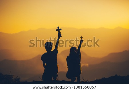 Two people sitting holding christian cross for worshipping God at sunset background. christian silhouette concept.