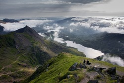 Two people sitting on rock at top of Mount Snowdon looking down over dramatic lakes and valley