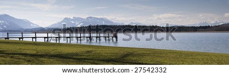 Two people sitting on the landing at the Chiemsee with the alps in the background. Panorama picture