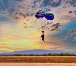 two people skydiving in tandem with a blue parachute
