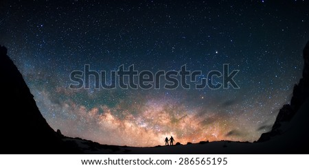 Two people standing together holding hands against the Milky Way galaxy in the mountains. Nepal, Himalayas, Everest region, Gokyo (4,790 m).