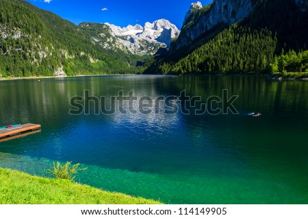 Two people swimming in alpine lake with crystal clear green water and mountains in the background, Gosausee, Austria