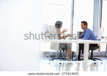 Shutterstock Two people talking in an office