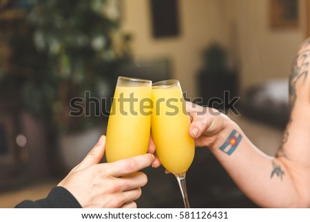 """Two people tapping their beverages together for a """"cheers"""" moment. Two drinks with orange juice and champagne, also known nas a mimosa."""