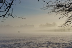 Two people walking across an eerie public field after heavy snowfall on a misty January morning, The Stray, Harrogate, North Yorkshire, UK.